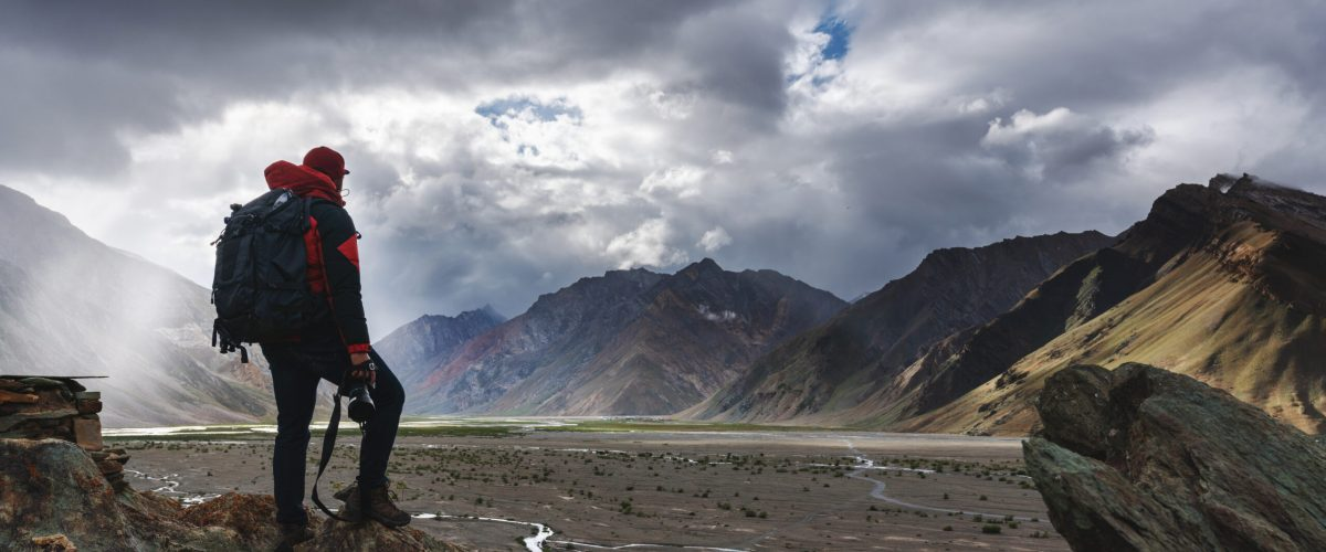 a man with backpack holding camera standing on cliff with mountains view and sunlight through cloud. Travel lifestyle, adventure and success concept